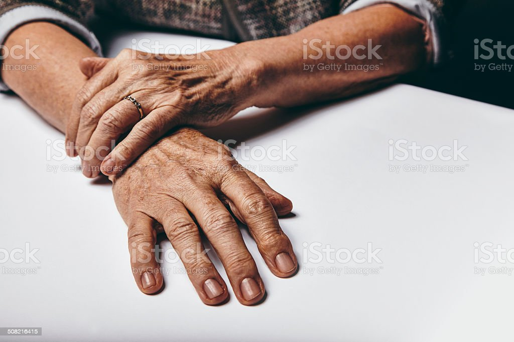 Old female hands on a table royalty-free stock photo