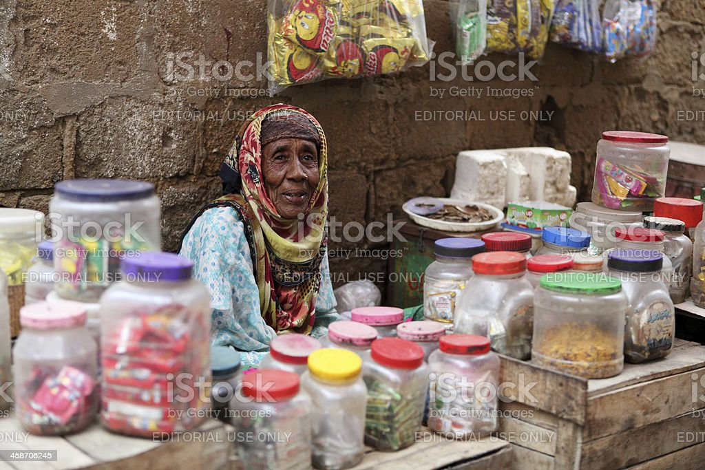 Old female street sweet vendor sits outside her home stock photo