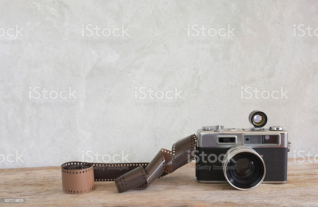 Old film camera and a roll of film on wood stock photo