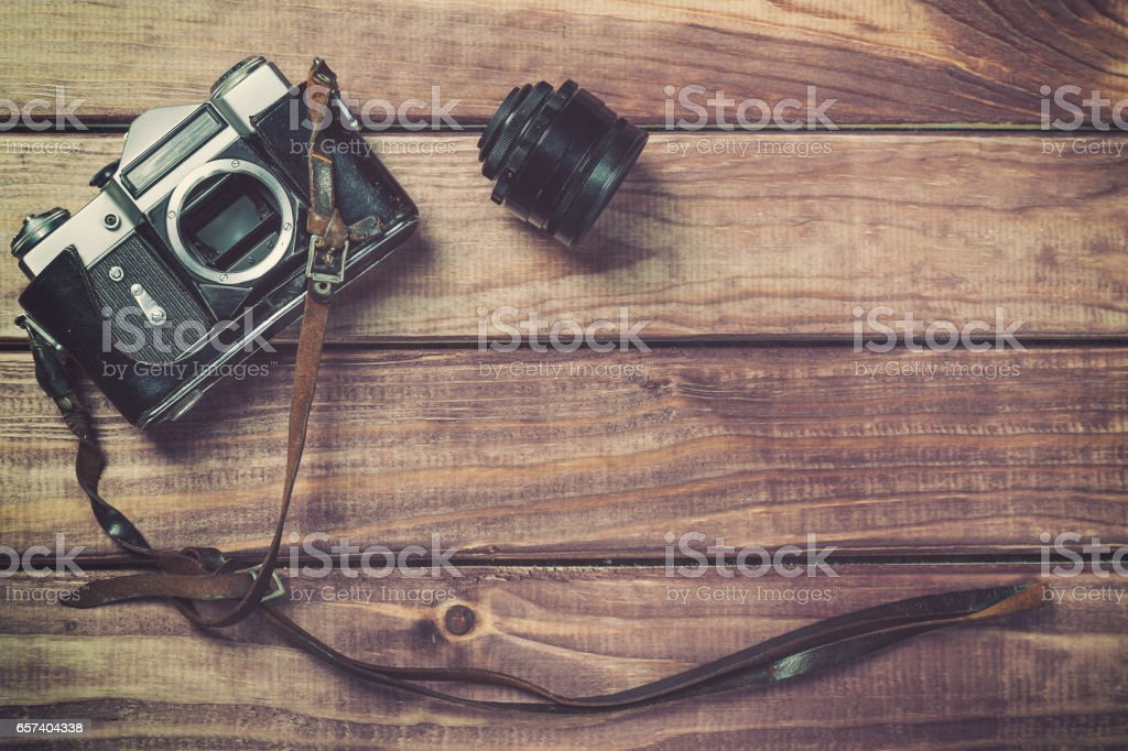 Old film camera with strap and lens on wooden background. Vintage toned and top view with free space stock photo