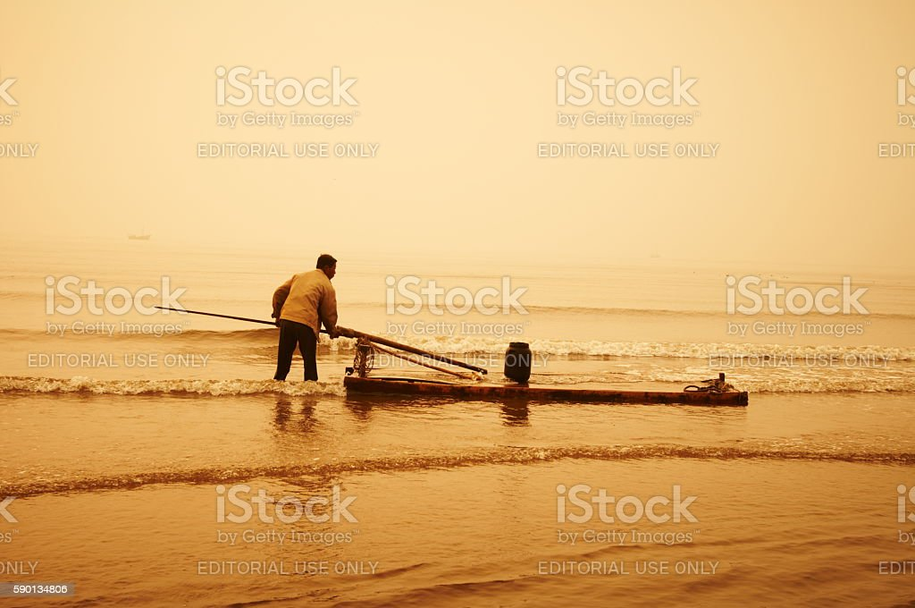 Old fisherman on a raft in the Yellow Sea. stock photo