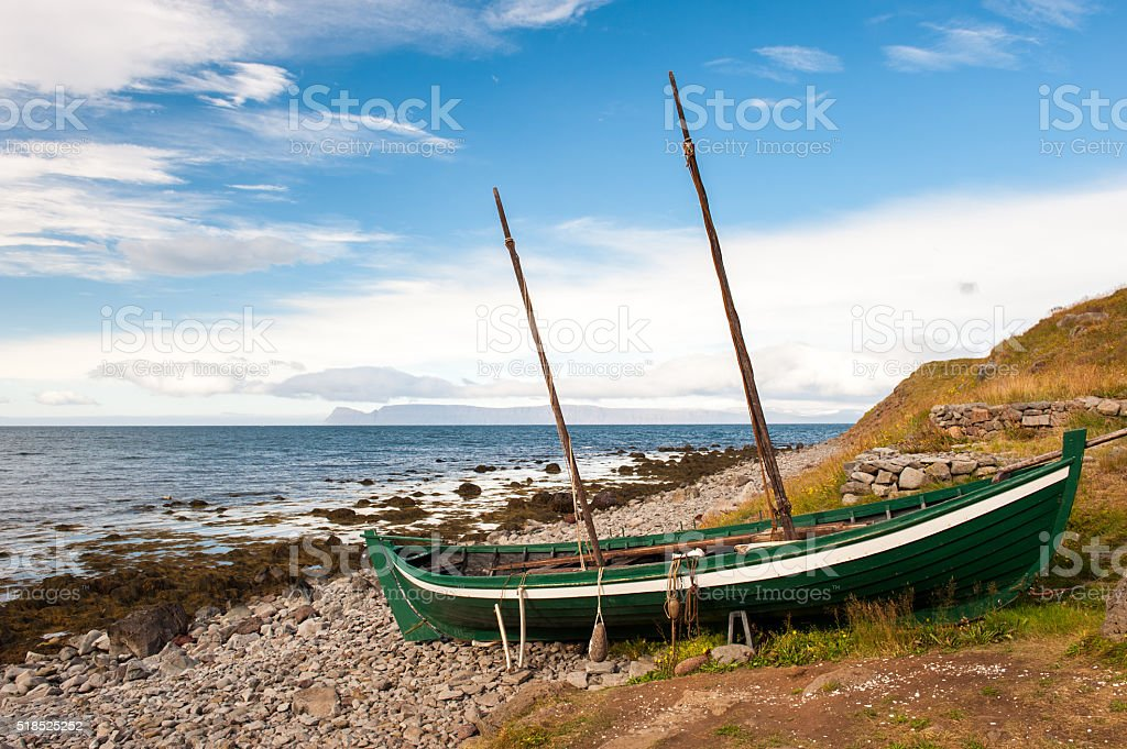 Old fishing boat, boat of the Vikings on the ocean shore, Iceland stock photo