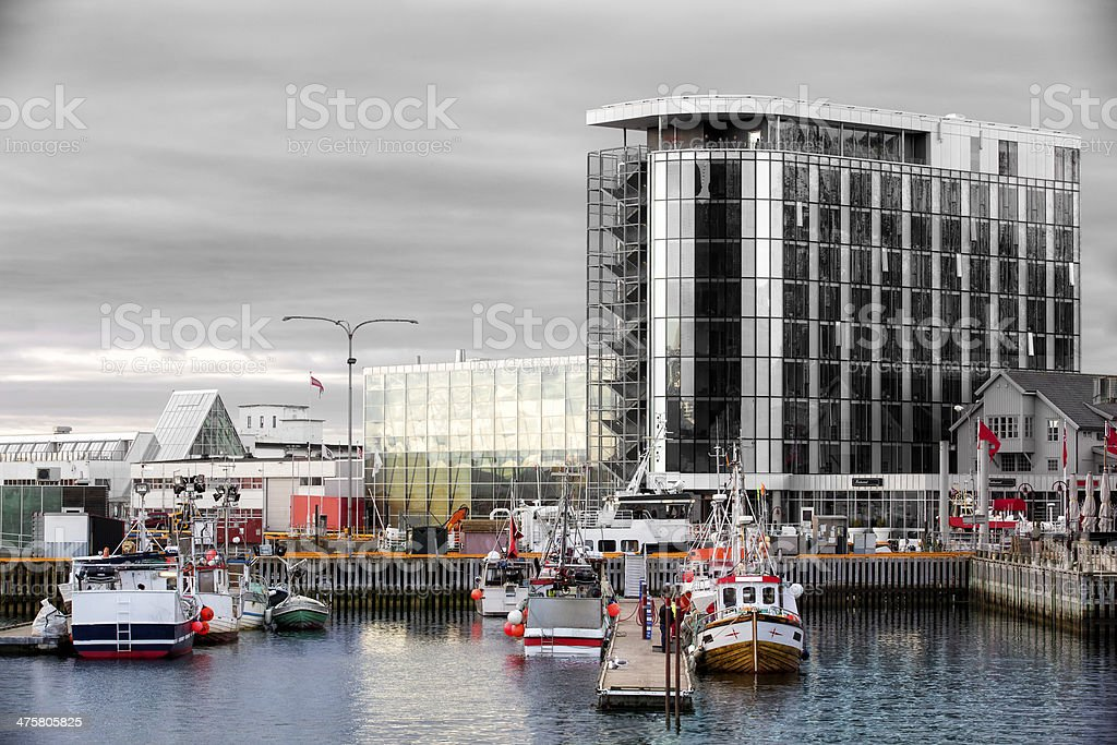 Old fishing boat in front of modern hotel at Svolvaer royalty-free stock photo