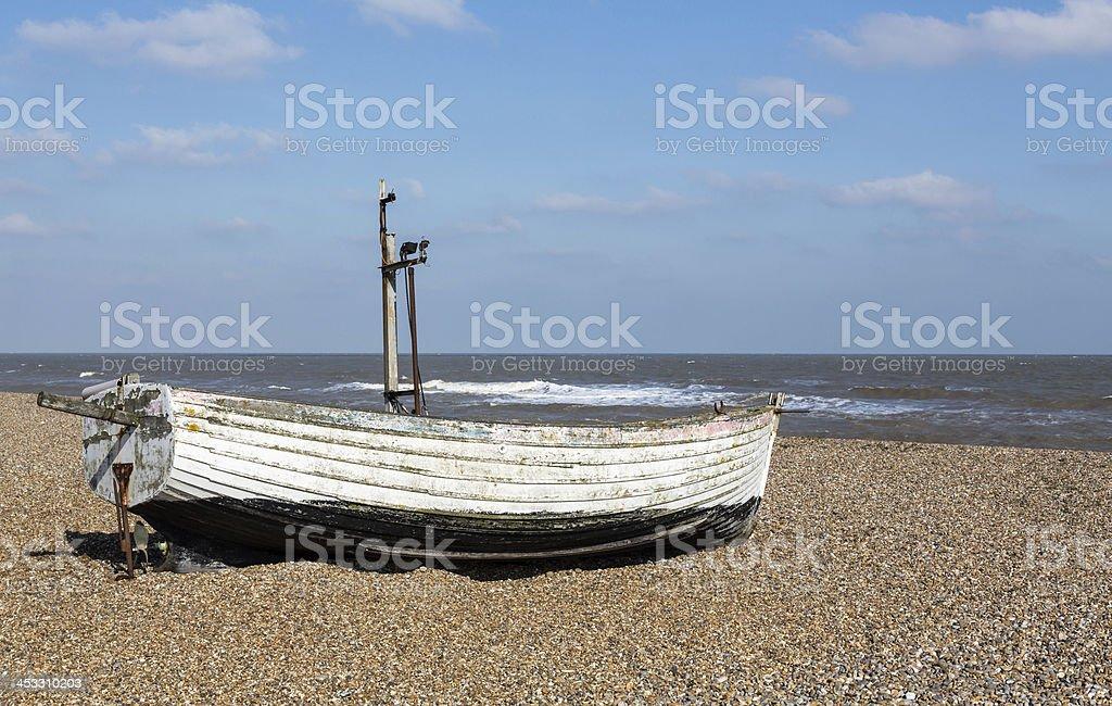 Old fishing boat on pebble beach stock photo