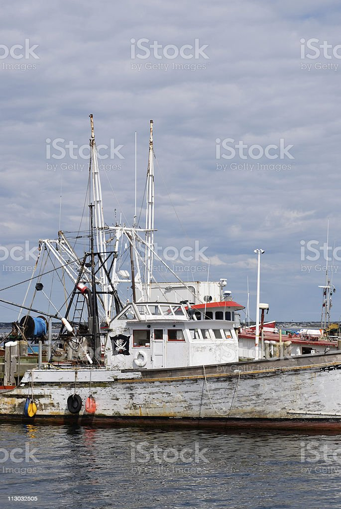 Old fishing boat with white peeling paint docked in harbor royalty-free stock photo