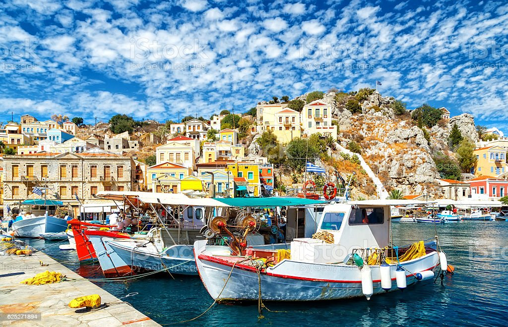 Old fishing Boats at Simi , background of beautiful multi-colored buildings stock photo