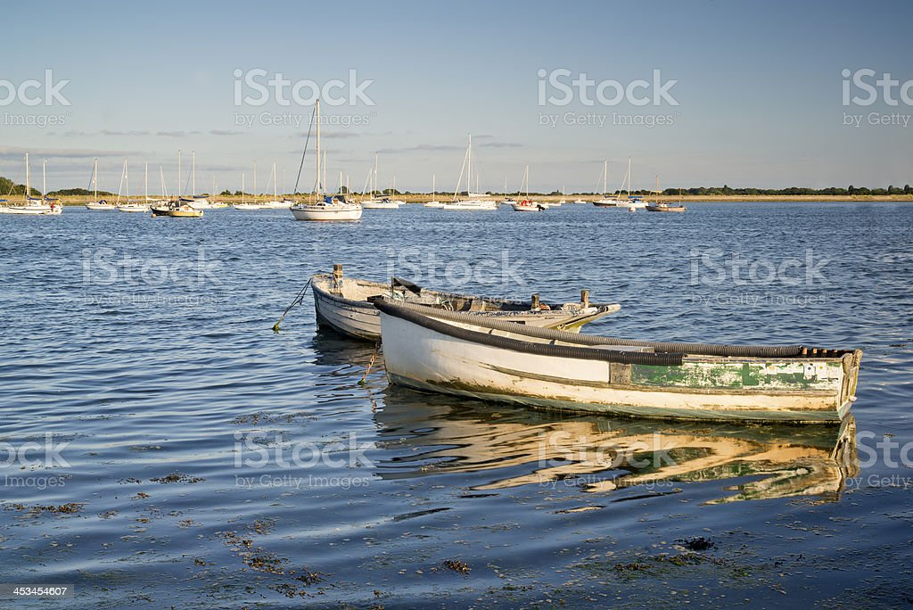 Old fishing boats reflected in calm water during Summer sunset royalty-free stock photo