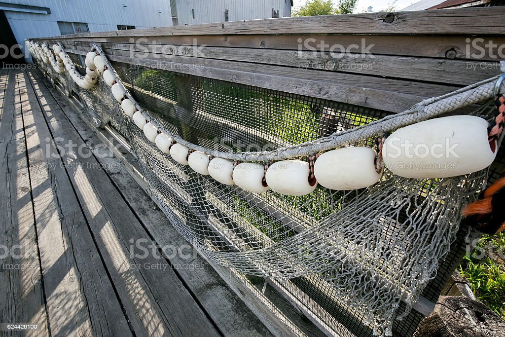 old fishing net hanging before a historic shipyard stock photo