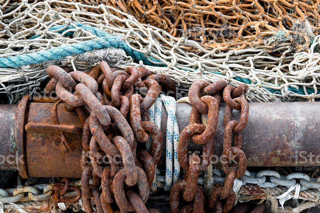 Old fishing net with ropes a rusty chain and winch stock photo