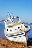 Old fishing vessel on the sea coast, Algarve, Portugal