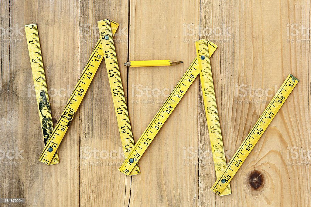 Old folded meter and pencil on plank wood stock photo