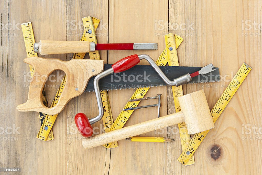 Old folded meter, wooden hammer, nails,hand drill and chisel royalty-free stock photo