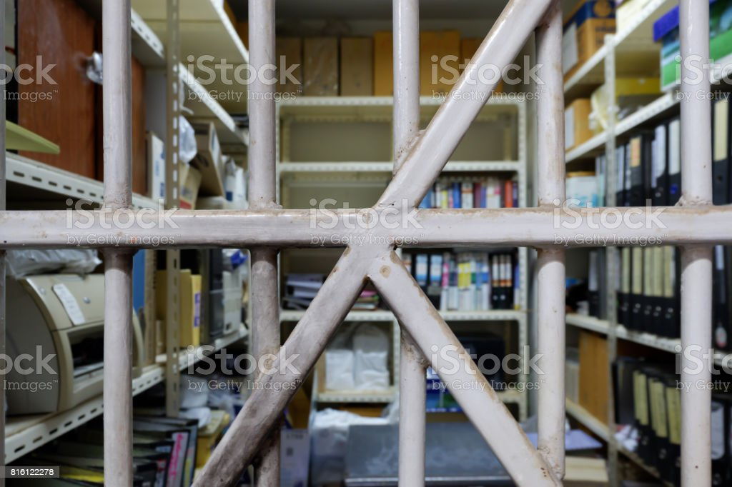 Old folder storage room seen through bars stock photo