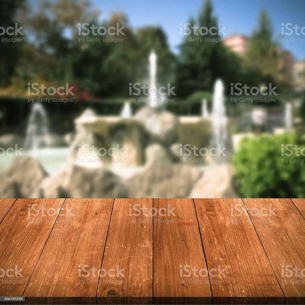 Old fountains in the park over old dark wooden table stock photo