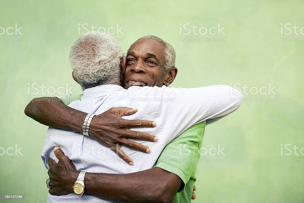 Old friends, two senior african american men meeting and hugging stock photo