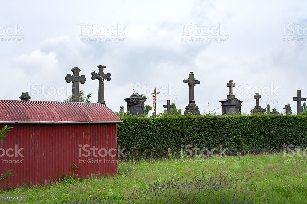 Old garden shed  with graveyard behind hedge stock photo
