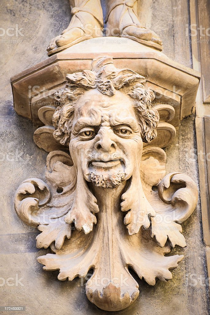 Old Gargoyle Head representing Nature under Warrior Feet royalty-free stock photo