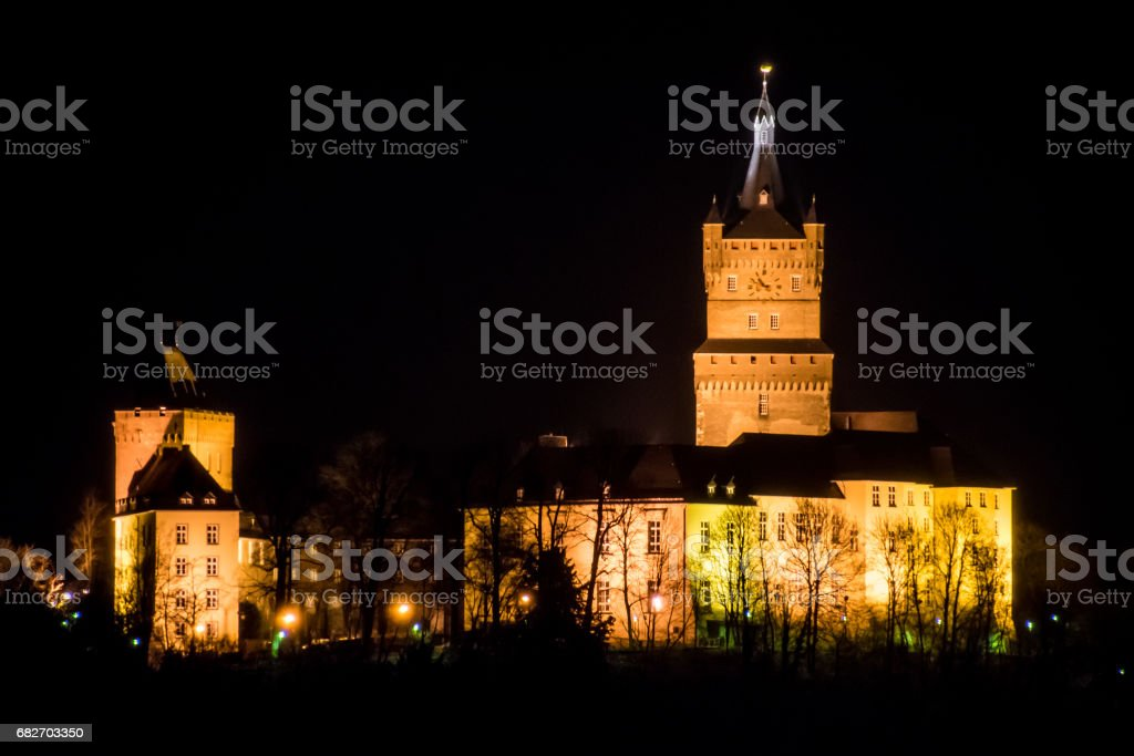 Old german castle tower clock palace at night stock photo