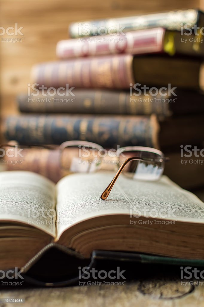 Old Glasses on Open Book, on Wooden Table stock photo