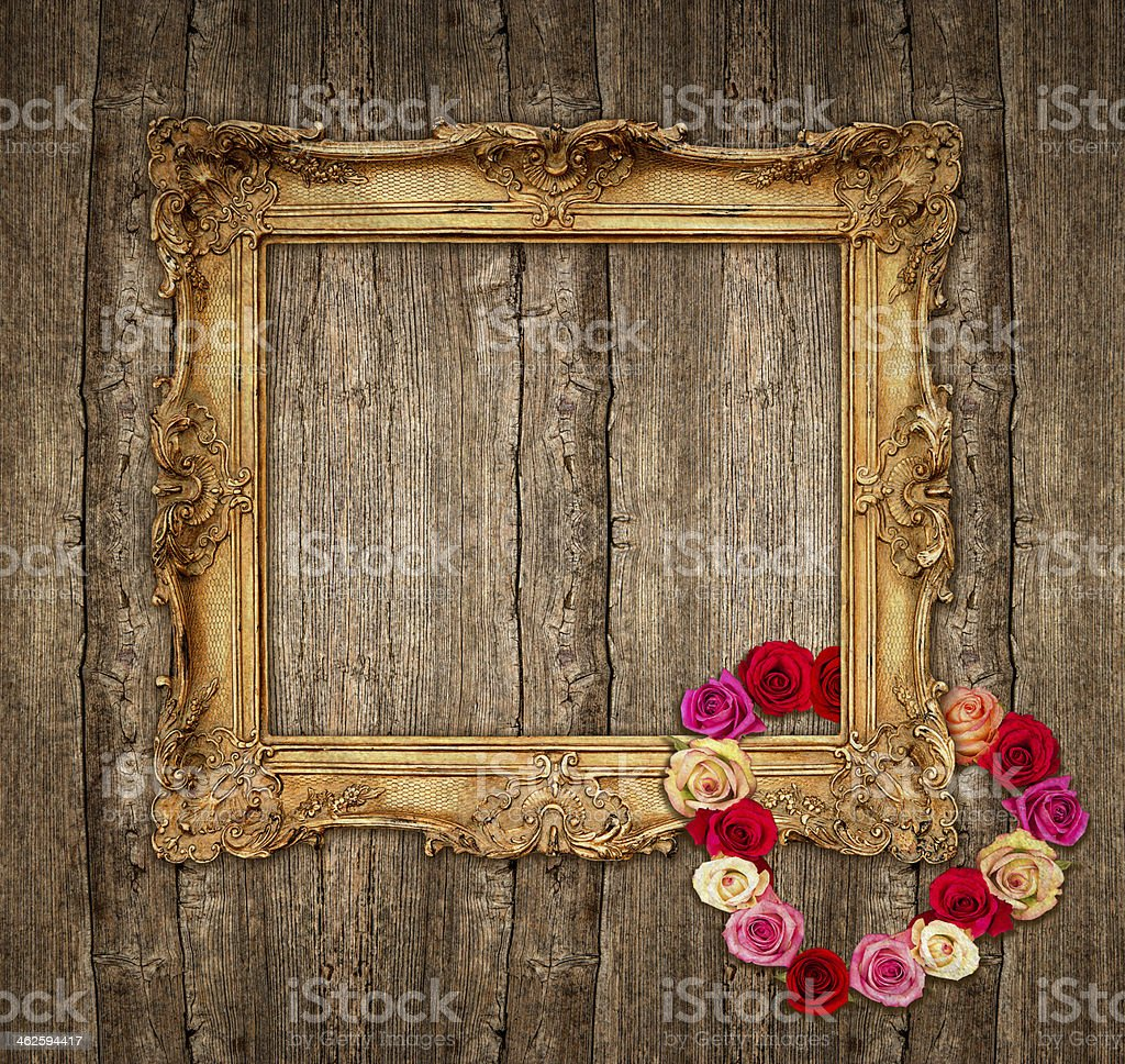 old golden frame with roses over wooden background stock photo