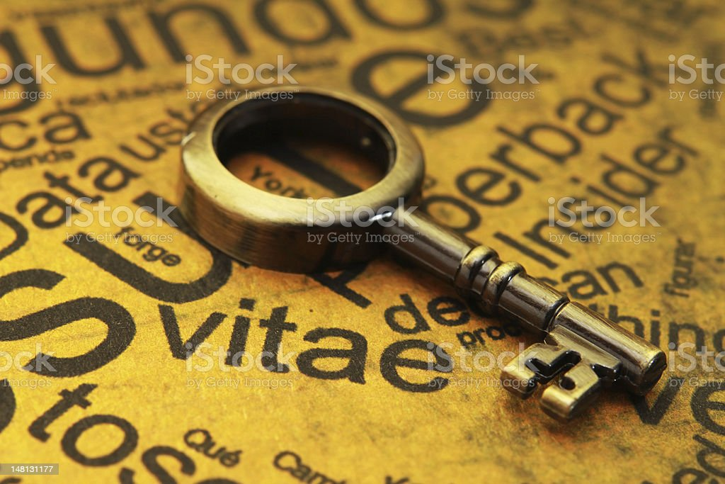 Old golden key over dirty yellow paper in close-up stock photo