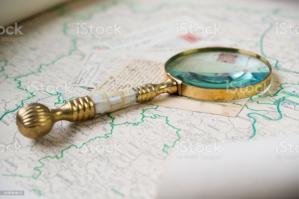 Old golden magnify glass on ancient post cards, old map stock photo
