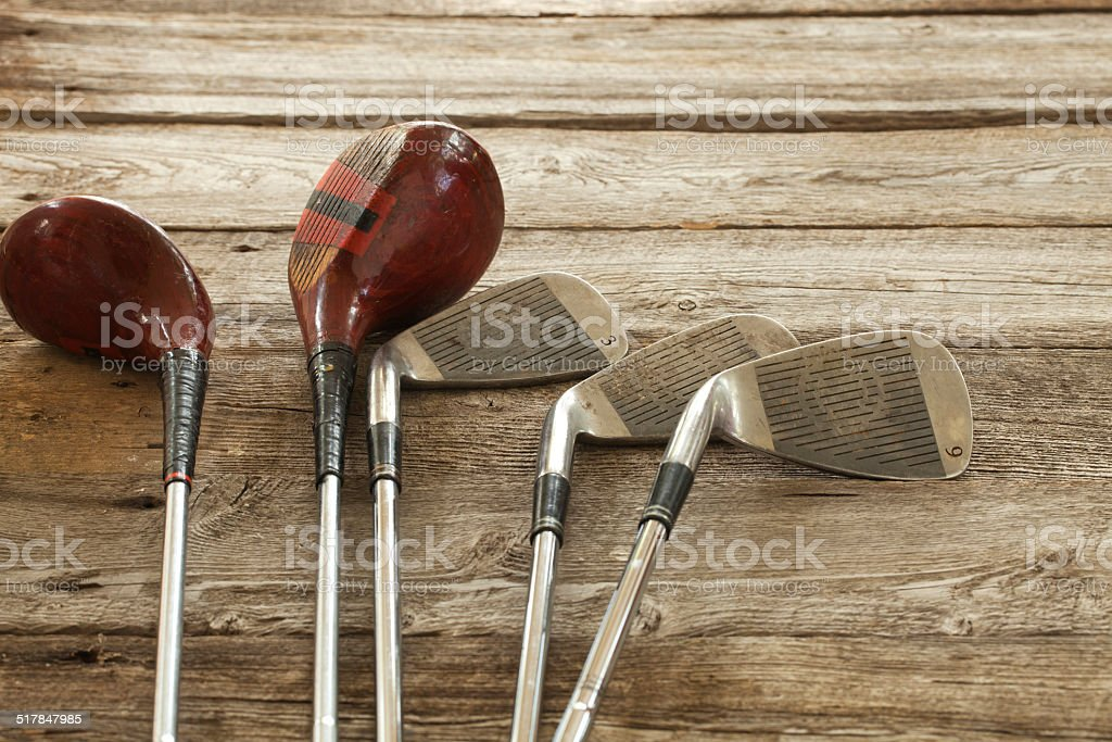 Old golf clubs on rough wood surface stock photo