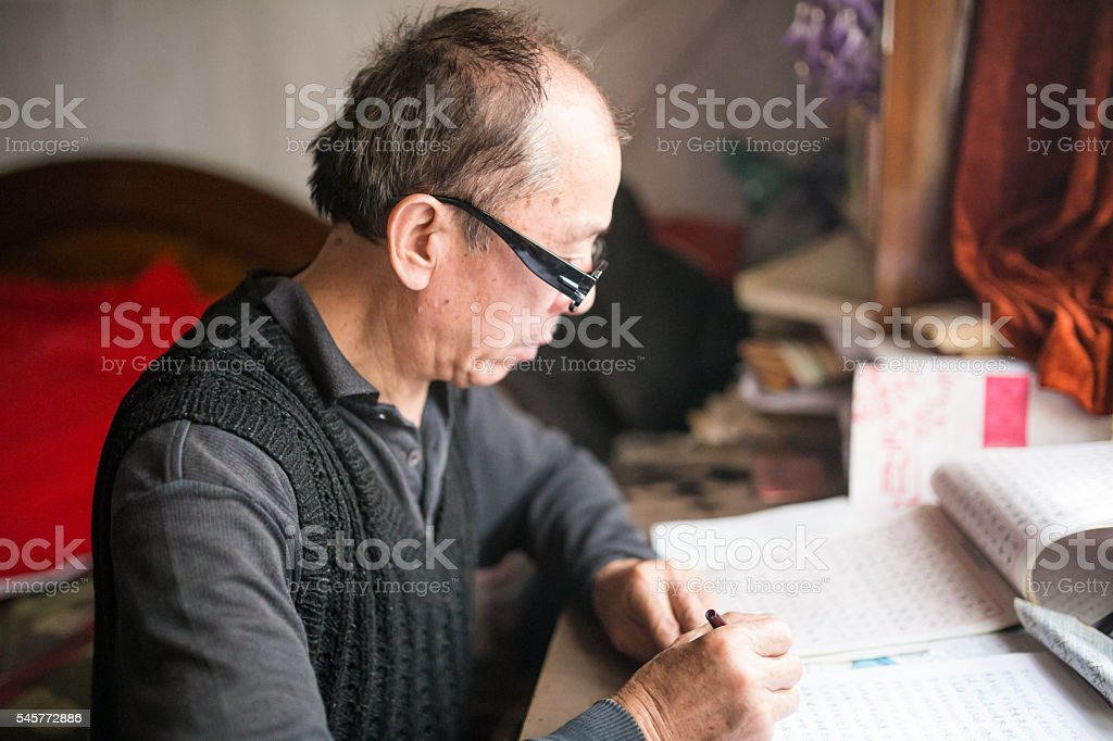 Old grandfather writing letter at home stock photo