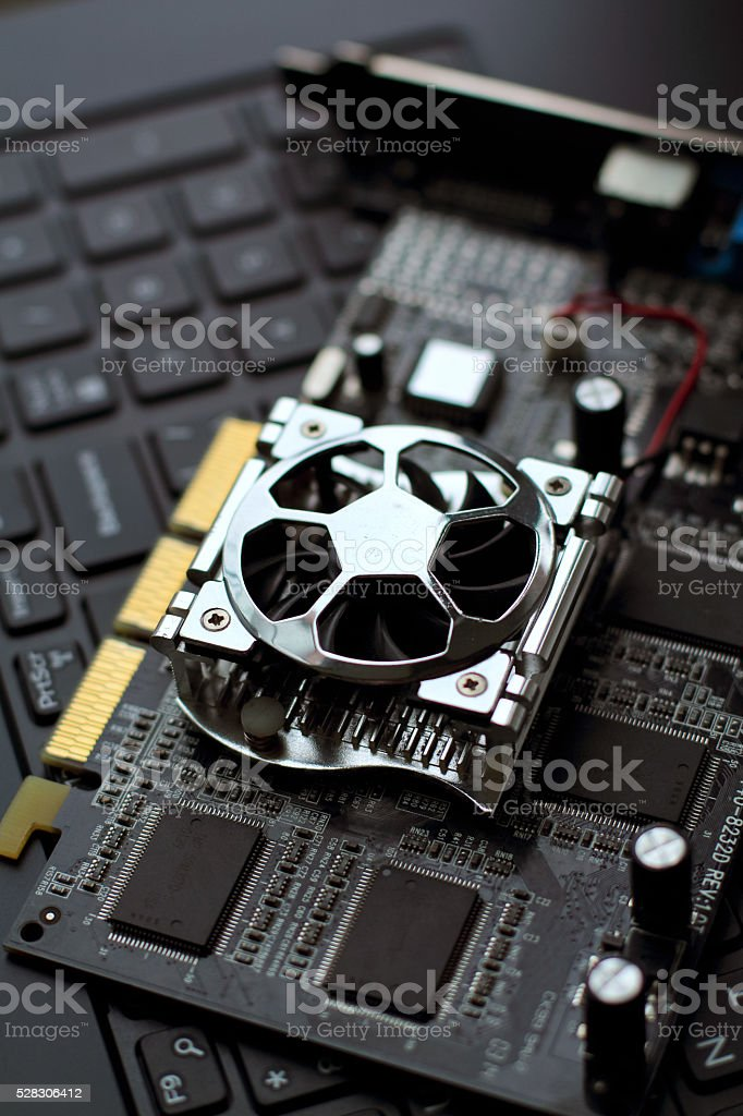 old graphics card lays on the black keyboard stock photo
