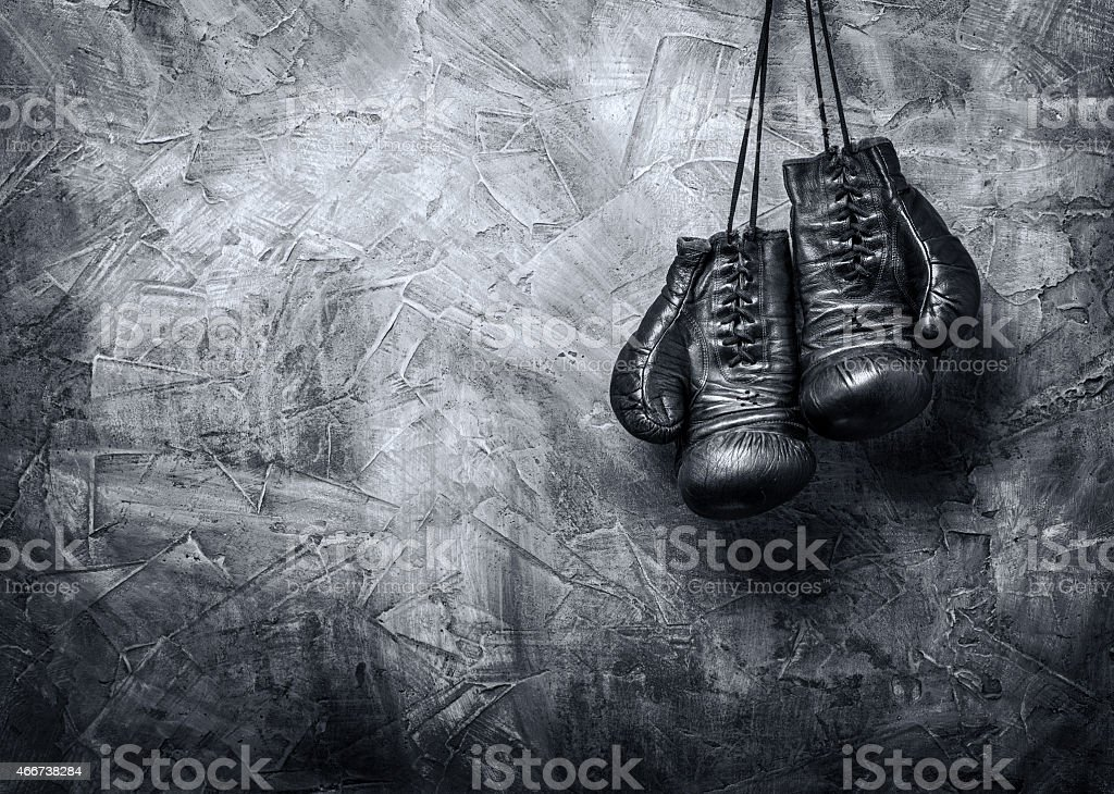 Old gray boxing gloves hanging up stock photo