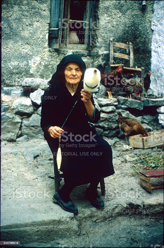 Old Greek Woman Spin front of their home stock photo