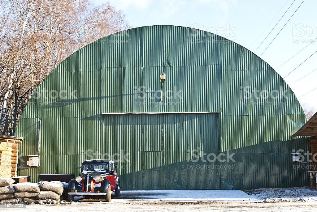Old green aircraft hanger with classic car park in front stock photo