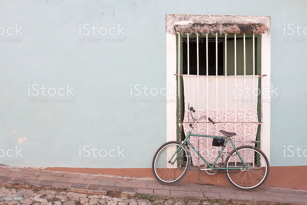 Old Green bike leaning against blue wall royalty-free stock photo