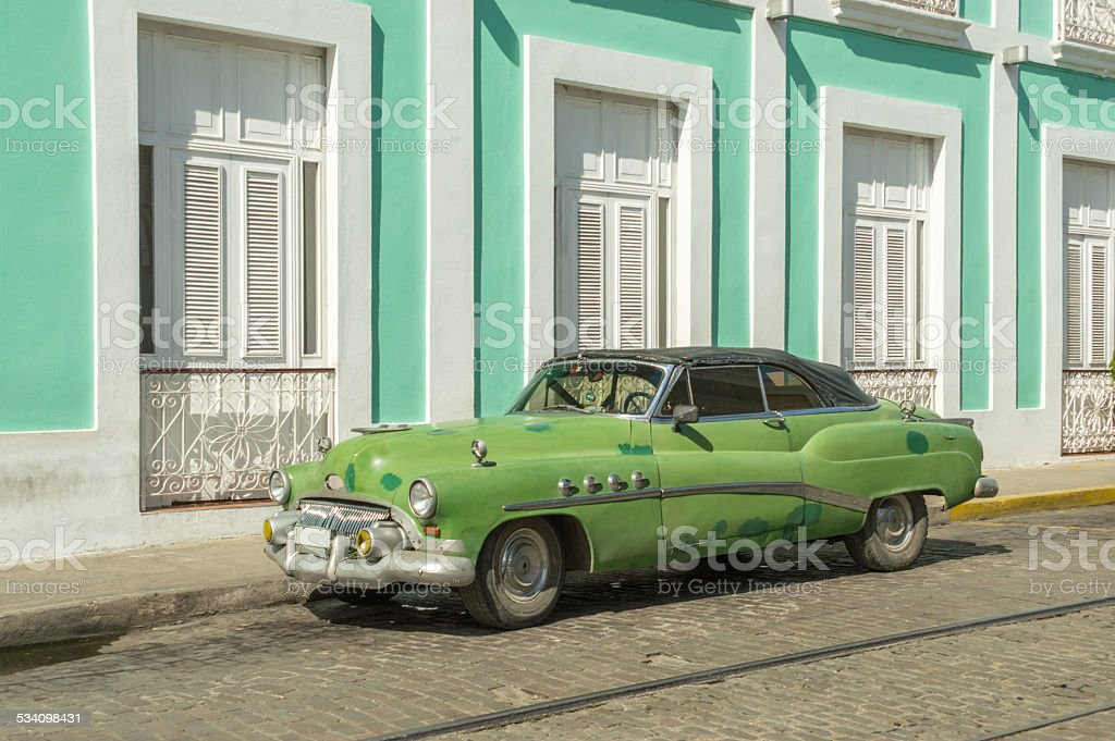 Old green car in front of a mint green building stock photo
