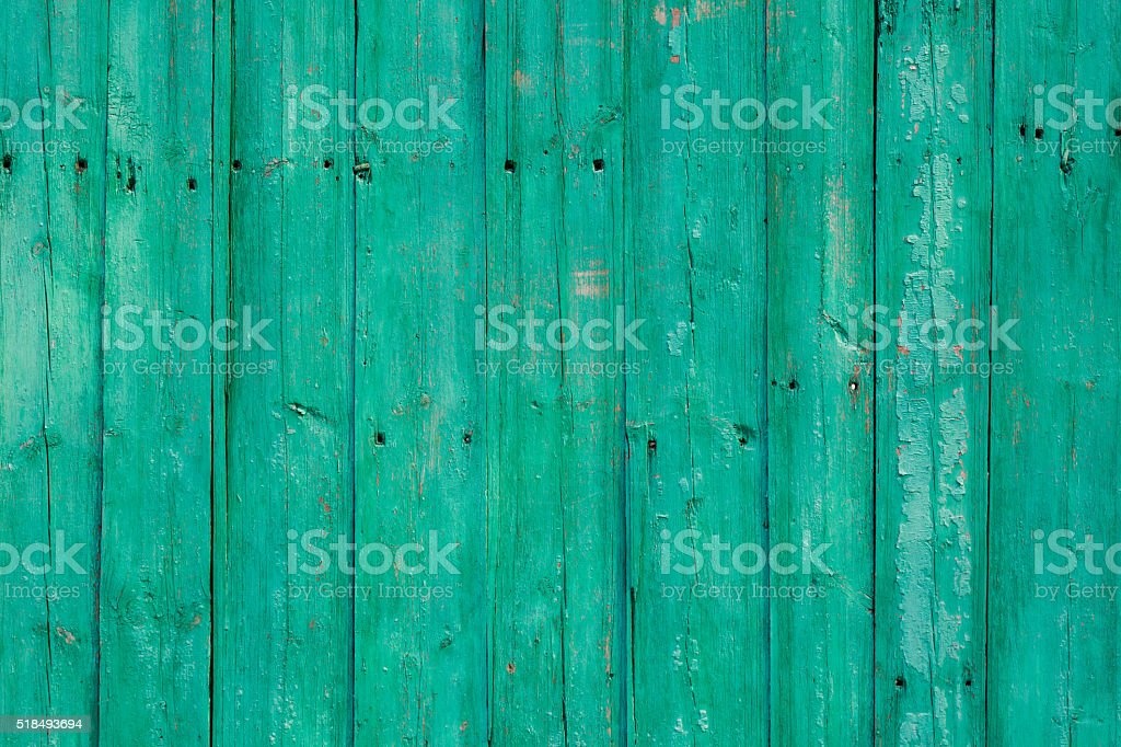 Old green cracked paint on wooden background stock photo