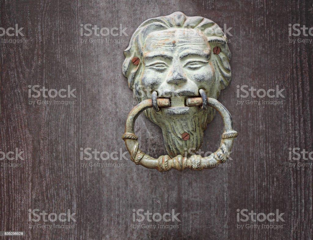 Old green Door knoker on an old wodden door stock photo