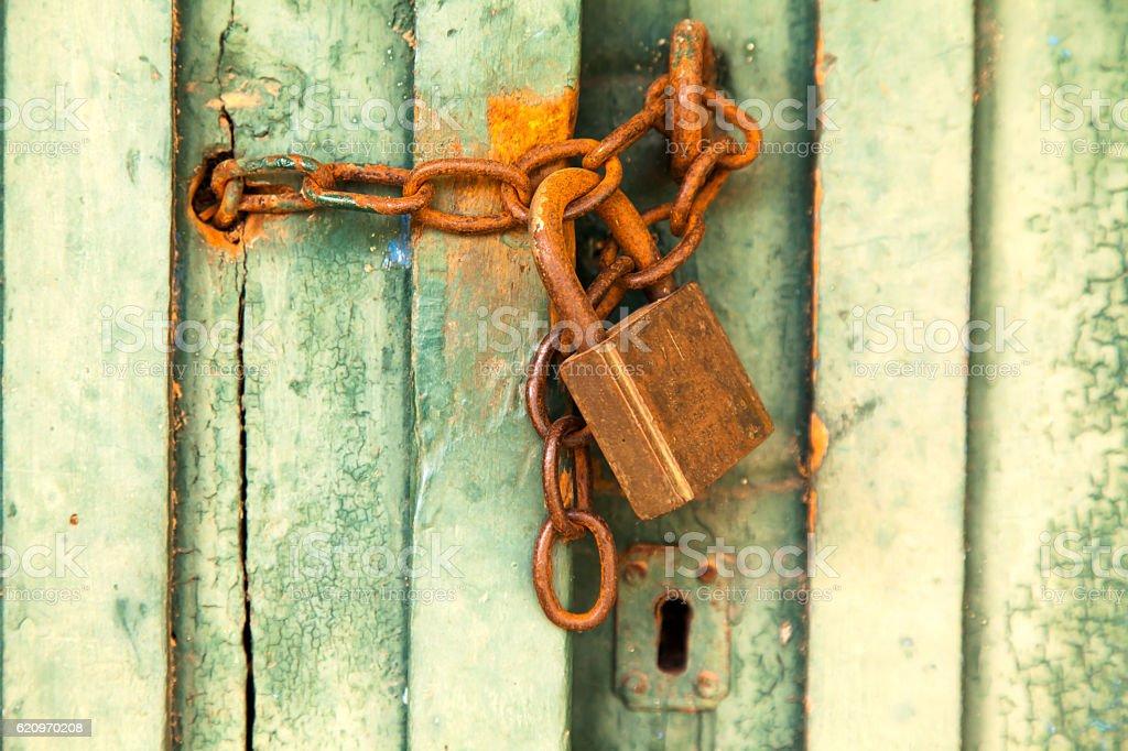 Old green rural door with rusty padlock stock photo