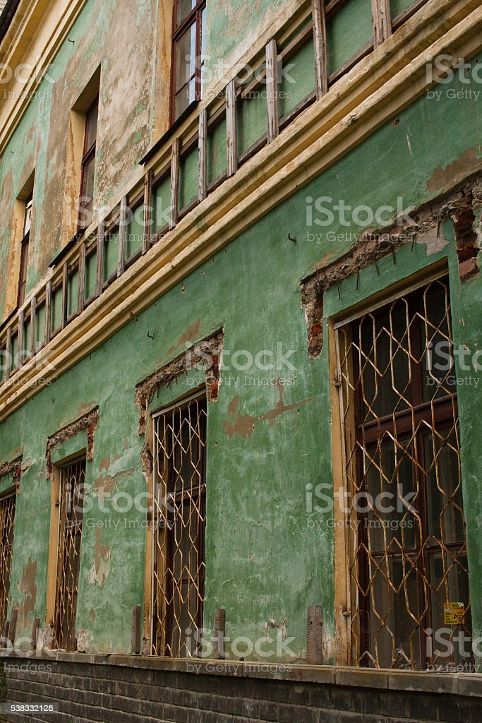 Old green shabby wall of an abandoned building stock photo