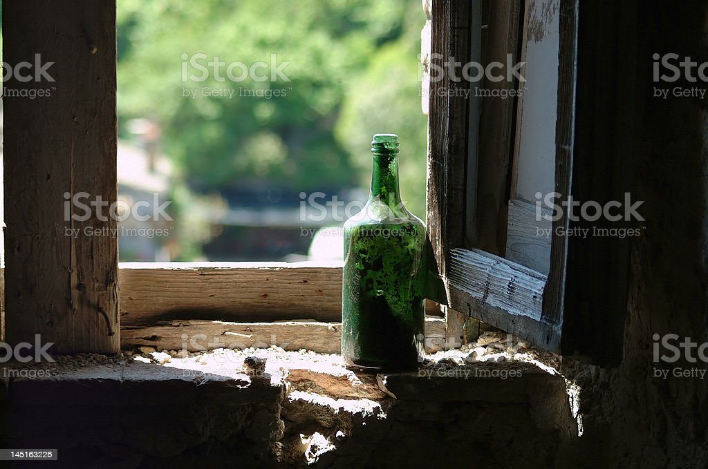Old green wine bottle in window royalty-free stock photo