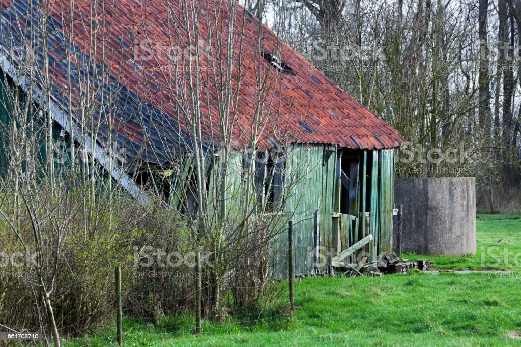 Old green wooden barn with red roof tiles stock photo