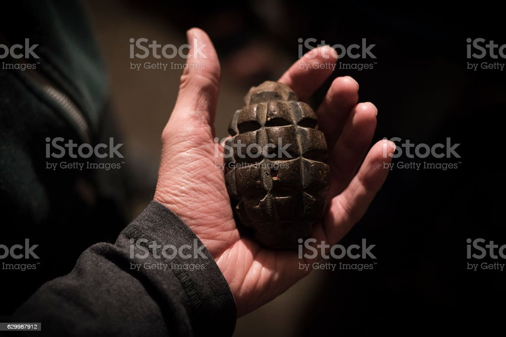 Old grenade held in hand's open palm stock photo