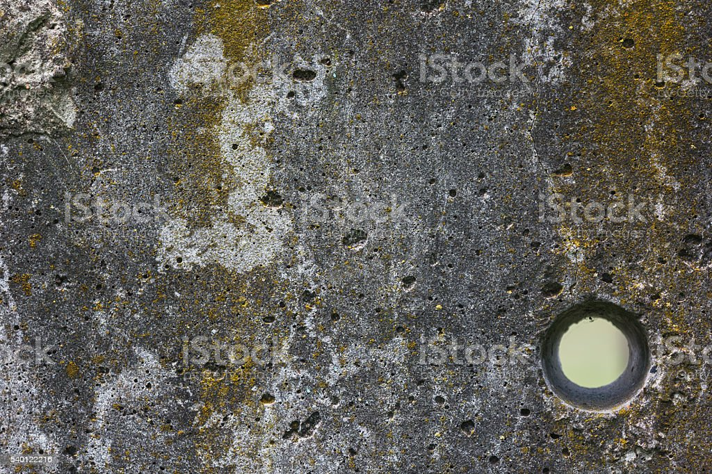 Old grey stone wall with round hole stock photo
