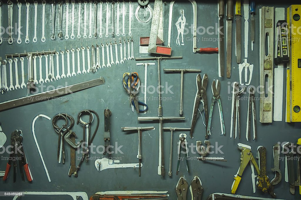 Old group of different hand tools hanging on the board. stock photo