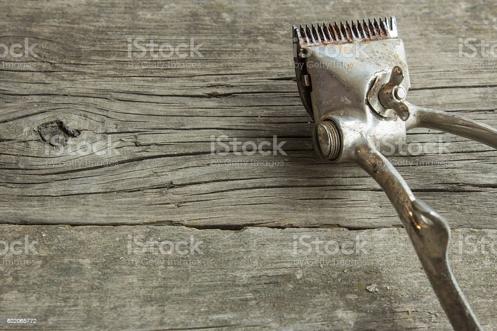 Old hairclipper on  wooden desk. Scratches, rust, not electric stock photo