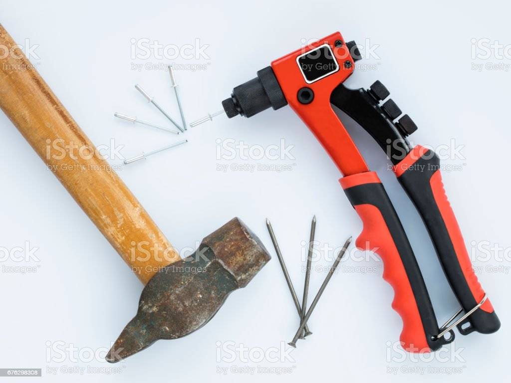 Old hammer and nails against new Rivet Gun and Rivets stock photo