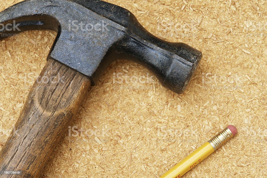 Old hammer and no. 2 pencil on particle board royalty-free stock photo