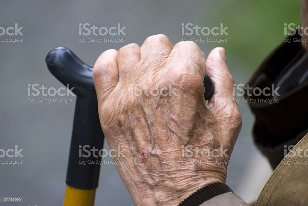 Old hand holding a walking stick stock photo