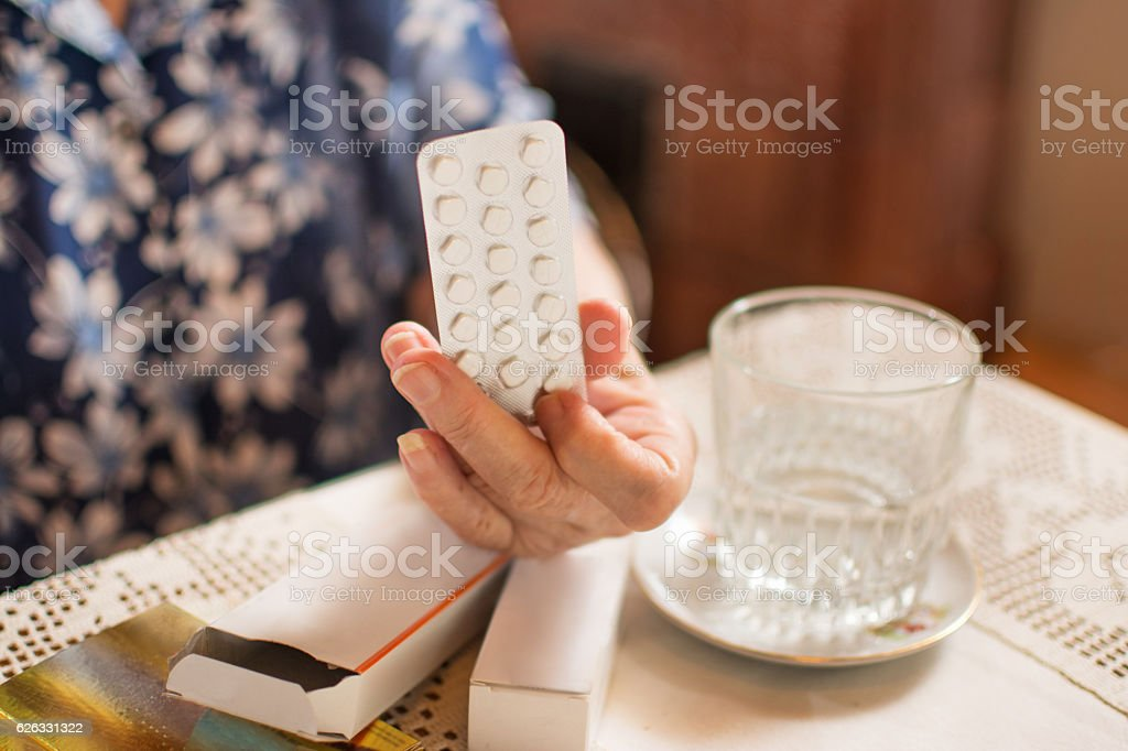 Old hand holding tablets near a glass of water. stock photo