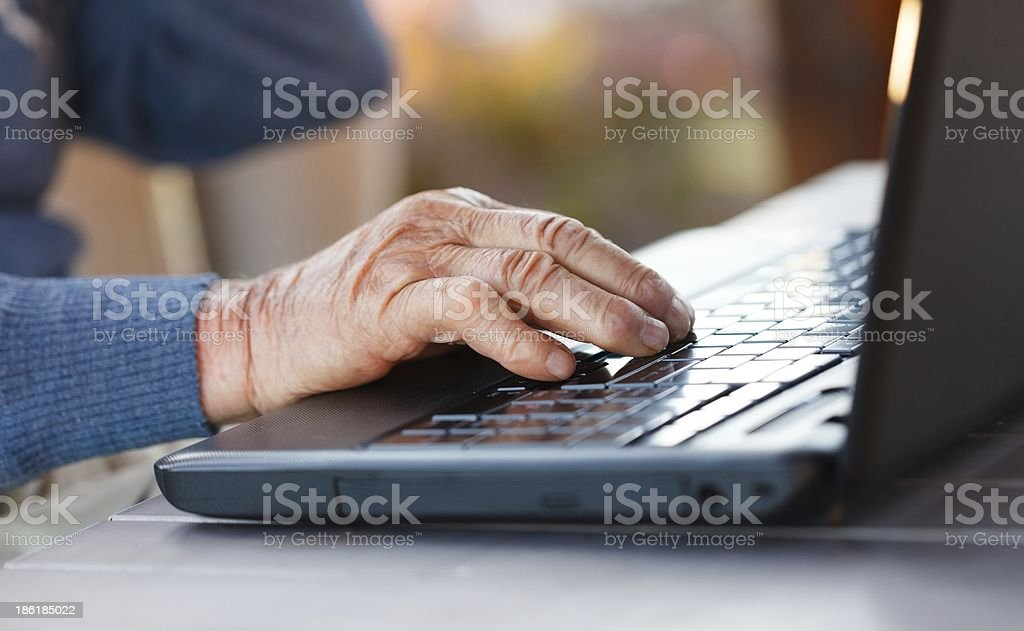 Old hand on a laptop stock photo