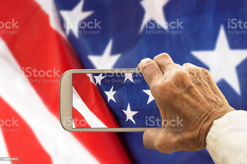 Old hand takes a picture of USA flag, stock photo